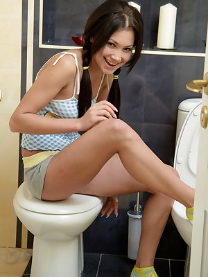 Cute brunette fucking a dildo in the bathroom