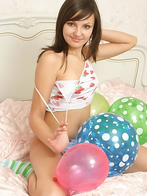 Cute brunette in her bedroom with some balloons