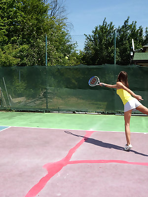 Charming brunette Candice Luca poses playfully on the tennis court, penetrating herself with the racket and a glass dildo