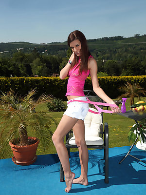 Candice Luca hangs out in the yard wearing a mesh top and short shorts with suspenders, shortly stripping down to unveil her tempting mounds and clit jewelry before toying her pussy with a cucumber and banana