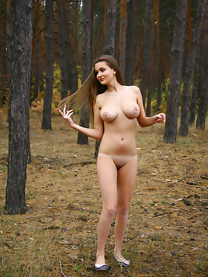 Newcomer Sanya bares her naked body and large tits as she poses in the forest.