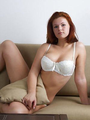 Newcomer Feya flaunts her large tits with erect nipples as she poses on the couch.