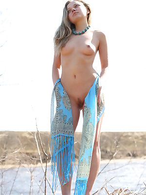 Tania C sensually poses outdoors as she bares her nubile body with puffy tits.