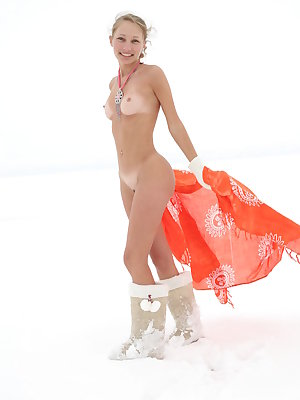 Mascha bares her petite body with tan lines as she poses in the snow.