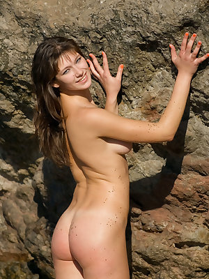 Valera shows off her luscious body by the rocky beach.