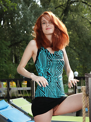 Redhead Alisa shows off her long, slender body outdoors.