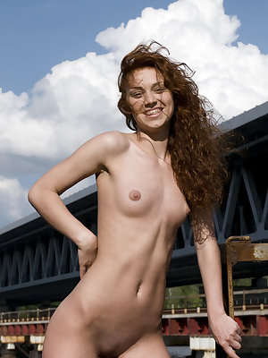 Talia A playfully poses by the bridge baring her petite body with small tits and smooth pussy.