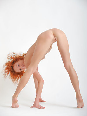 Natalie Red flaunts her slender, naked body with small puffy breasts and sweet pussy as she poses in front of the camera.