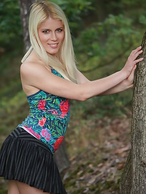 Jini flaunts her naked, slender body as she playfully poses outdoors.