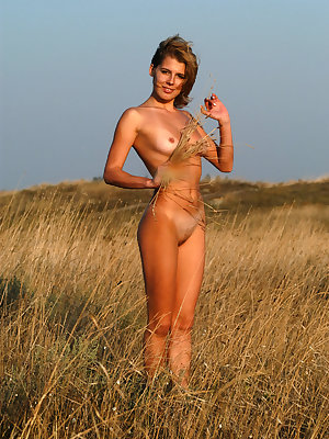 Newcomer Alina N sensually poses on the grassy field as she flaunts her sexy, tanned   body.