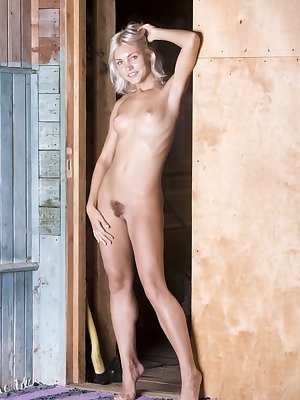Kristy sensually poses by the door as she displays her petite body and unshaven pussy.