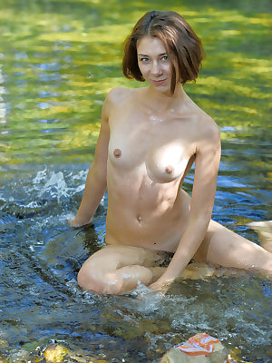 Oda palyfull poses as she dips her petite body and yummy pussy in the river