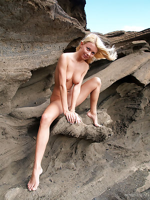 Judit bares her slender body with beautiful puffy breasts as she poses on   the sand.