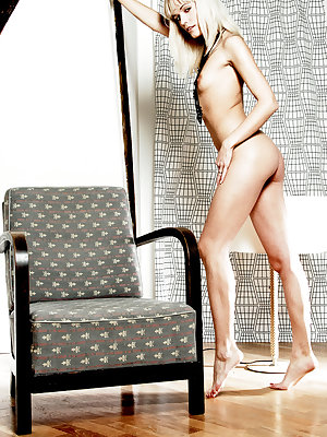 Susan A bares her naked, petite body with small   puffy breasts as she poses on the chair.