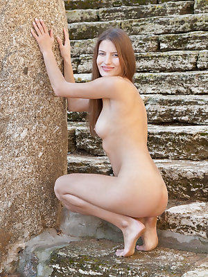 New model Monika F showcasing her lean, petite body and intimate details by the stairs outdoors.