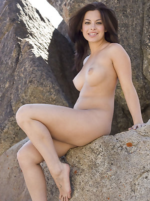 Seductive Oleen showcases her curvy body with big, puffy breasts and delectable pink pussy all over the rocky terrain.