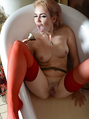 Monroe is a stunning and alluring blonde pin-up retro beauty.  Adorned in bright red stockings with seams up the back, she steps into the bathtub for some fun with the water massager.  She lies back in the tub and spreads her legs to expose her hairy puss