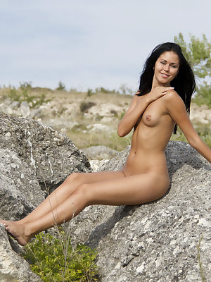 Jubia's confidently flaunts her naked body and poses on large rocks outdoors.