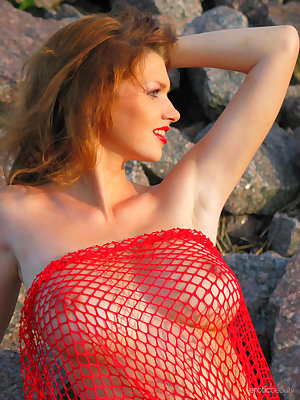 Beautifully exotic Maria D wears red netting at the beach and lets her large natural tits hang free.