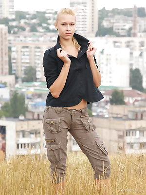 Angie basks outdoors in the soft sunlight undressing her black shirt and khaki pants showcasing her tight tanned body in an impressible display of feminine grace and confidence.