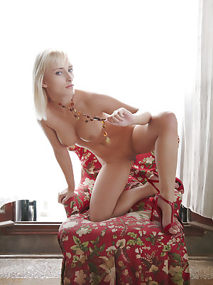Colette bares her creamy, curvy body with large breasts as she poses on the chair.