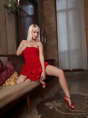 Sexy blonde Colette performs a seductive striptease by the sofa, showcasing her alluring and powerful sex appeal.