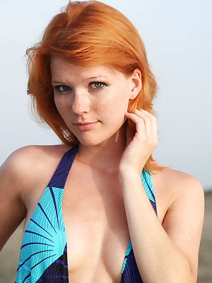 Classically beautiful redhead, Mia Sollis, poses in a blue swimsuit which compliments her ivory freckled skin and then sheds all to expose her delicate, shaved pussy, perfect breasts and overall stunning body.