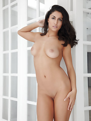 Exotic babe, Nadia, displays her full breasts and silky soft pussy lips all while seducing with her sultry eyes.