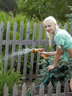 With a cute and charming smile on her pretty face, Leonie strips off her shirt and denim shorts in the garden before enjoying the refreshing cool water from th garden hose.