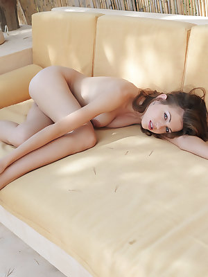 Eufrat sprawls invitingly on a beige sofa in an outside veranda, enjoying the warm mountain breeze and showcasing her petite body and pink details.