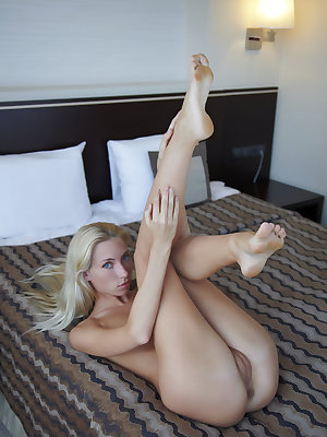 A naked Adele, with her pretty green eyes, looks straight to the camera with a tempting gaze as she poses confidently on top of the bed.