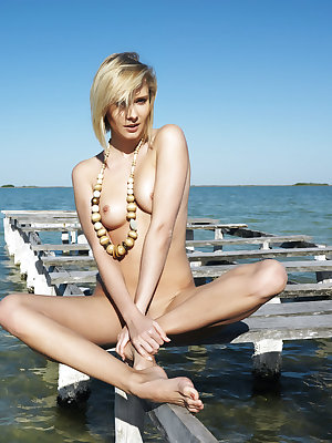 Deni throws all her cautions to the wind and enjoys a relaxing dip at the lapping water of the sea, her stunning body, sultry gaze and tempting look with irresistible tight details wet and moist.