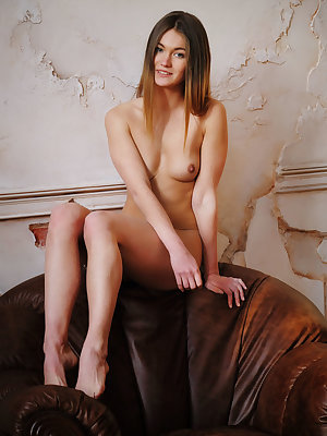 Solveig is naked sitting on the top of her brown overstuffed leather chair. She  spreads her legs wide open showing off perfectly proportioned petite body and delectable pussy.