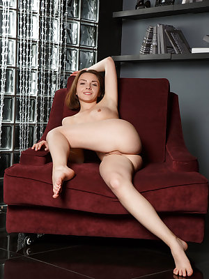 Una Piccola bares her tight body and smooth pussy as she poses on the couch.