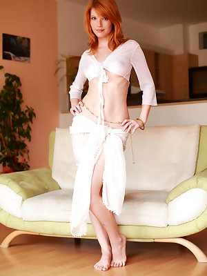 Redhead Mia Sollis shows off her pink pussy and beautiful puffy tits on the sofa.