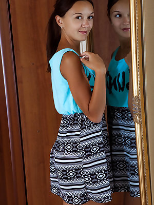 Veselin flaunts her petite, tanned body by the mirror.