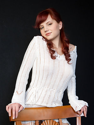 Absolutely stunning redhead with an amateur charm, perfectly molded breasts and super smooth fair skin that contrasts nicely to the chair she's sitting on.