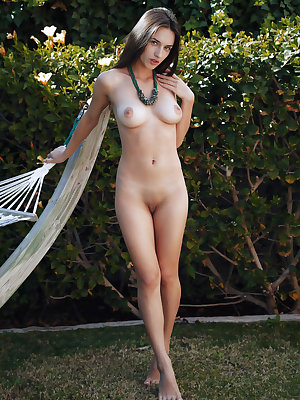 Gloria Sol relaxes in the garden hammock as she strokes her clit