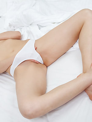 Sprawled naked on top of fresh white sheets, Leanisa's delicate beauty and nubile body looks temptingly delicious