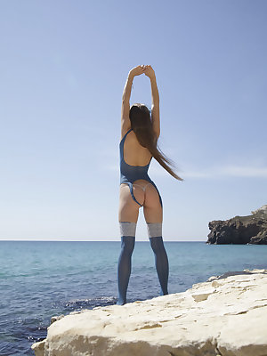 Petite siren Milena D posing in matching periwinkle blue lingerie and stockings by the beach