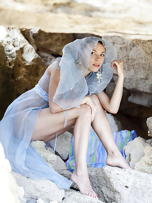 Eddison's delicate, nubile body stands out against the sharp, rough rocks by the beach.