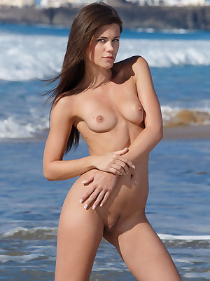 Caprice A sprawls naked on a sandy beach like a teasing, playful siren