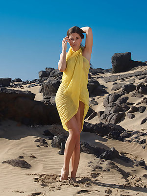 Caprice A plays amongst the craggy rocks wrapped in a yellow chiffon wrap.  As she unwraps herself, she presents her perfectly proportioned petite body your your enjoyment and admiration.  Caprice is a beauty to behold as she spreads her shapely toned leg