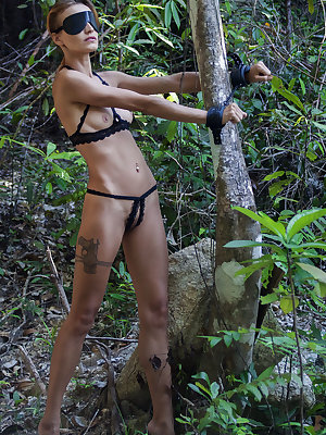 Newcomer Lesma flaunts her delectable pussy while being handcuffed in the forest.