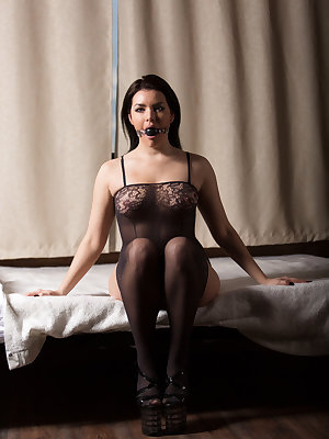 Bella A shows off her sexy lingerie as she masturbates on the bed with a gag   on her mouth.