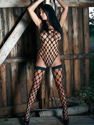 Rebeka flaunts her delectable assets as she sensually poses with her full-body fishnet   lingerie.
