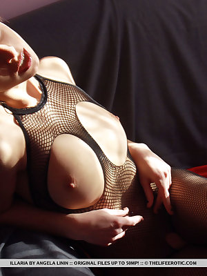 Illaria shows off her full body fishnet with holes baring her perky tits and delectable pussy as she poses on the couch.