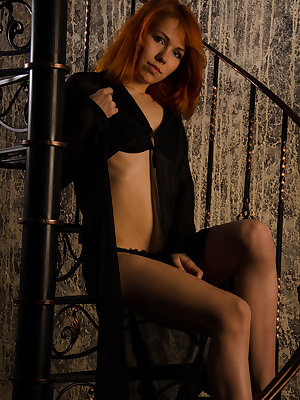Pretty redhead Kris B shows off her gorgeous body clad in sheer black cardigan and matching lingerie as she poses by the staircase.