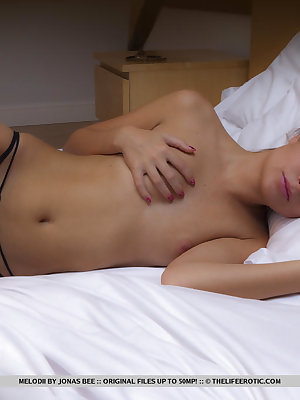 Melodii feeling aroused and sexy lay on the bed and started putting an erotic pussy fingering and masturbation with her pink dildo in her debut series.