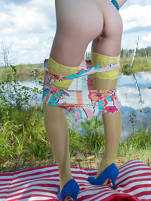 Stunning skinny teen plays around with her body on the lap of nature with the blue sky complimenting her beauty.